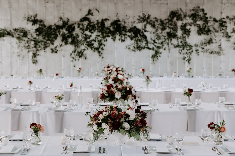 Blush and burgundy centerpieces with greenery wall