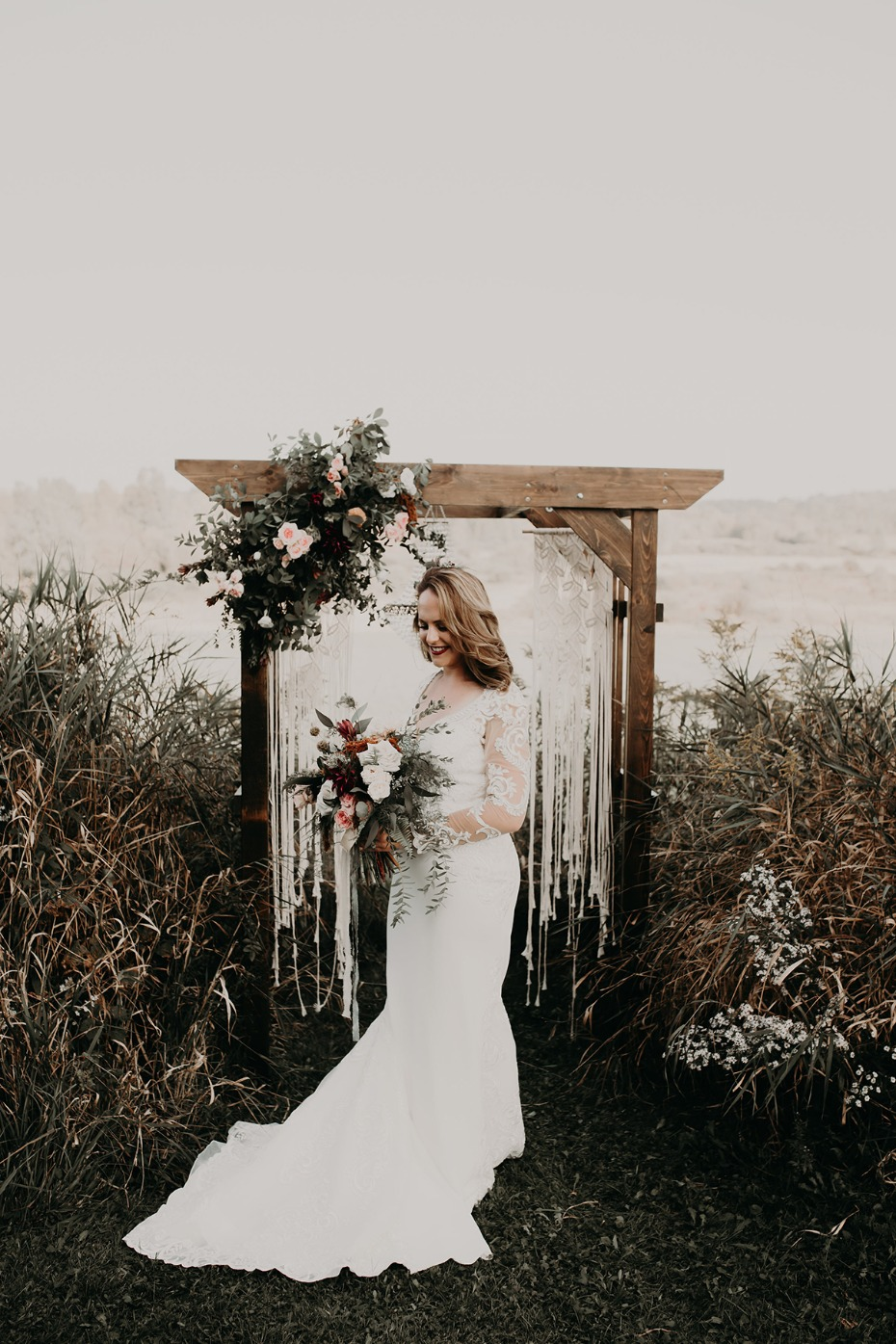 bride in front of a macrame wedding backdrop