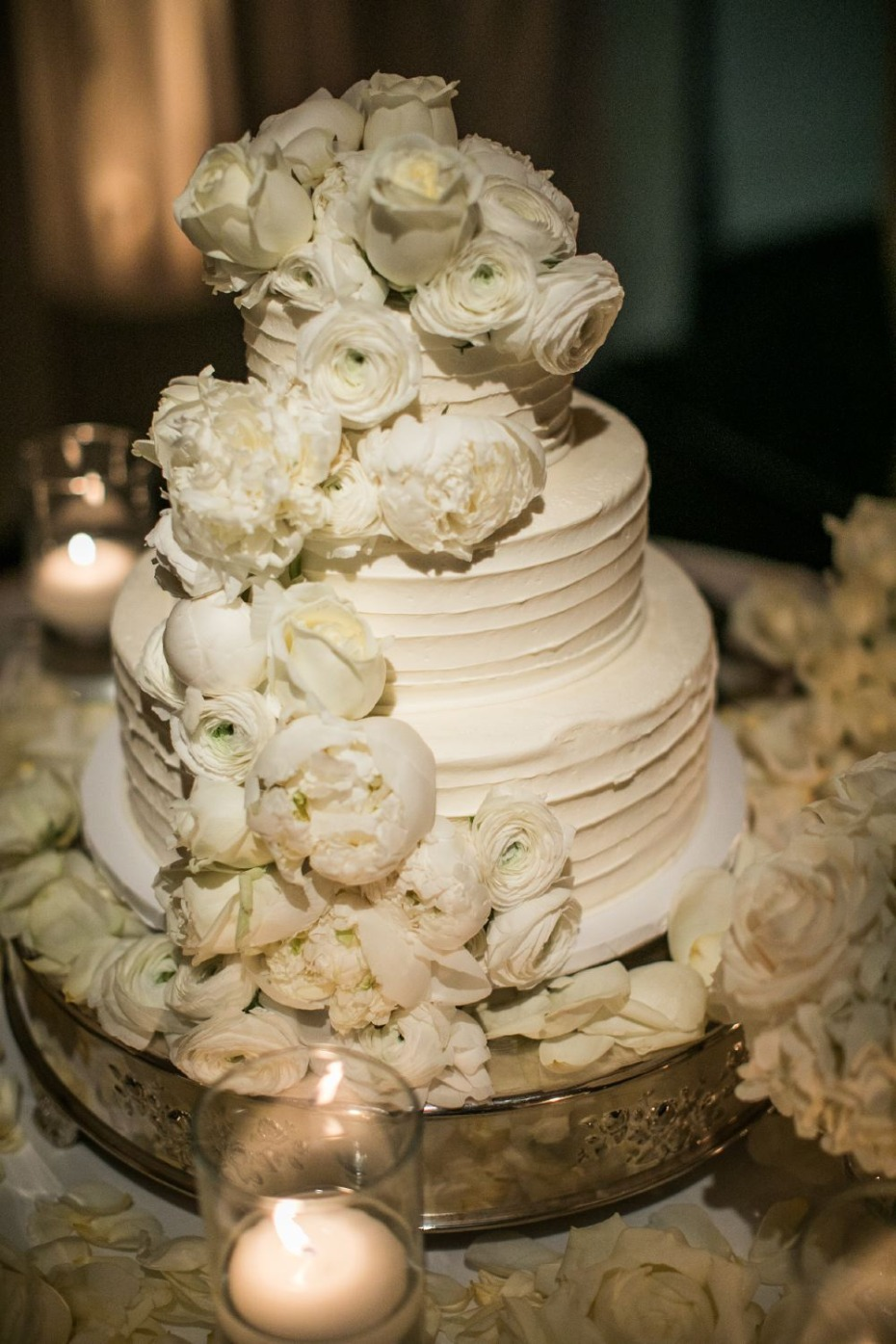 all white floral topped wedding cake