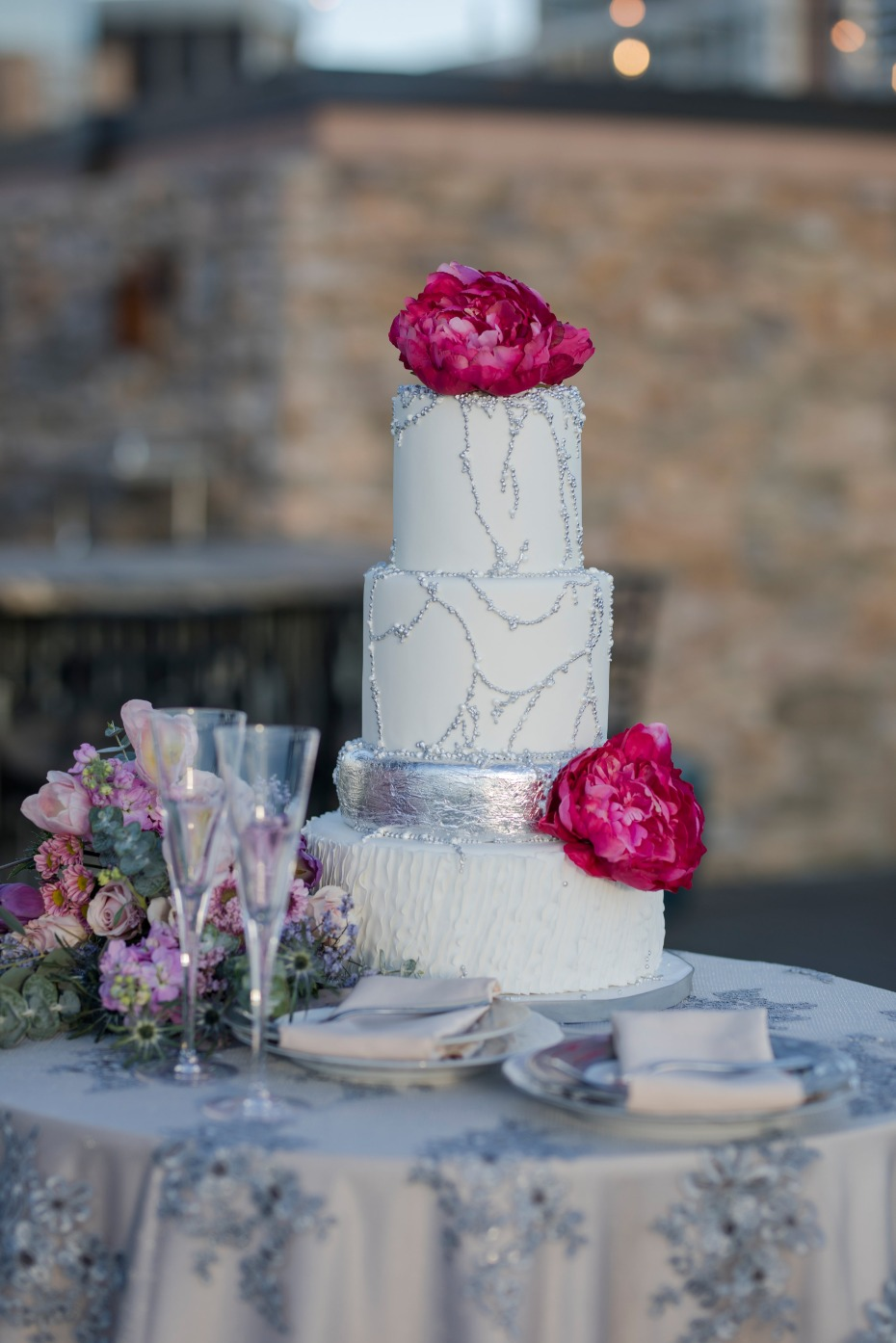 flower topped wedding cake with silver accents
