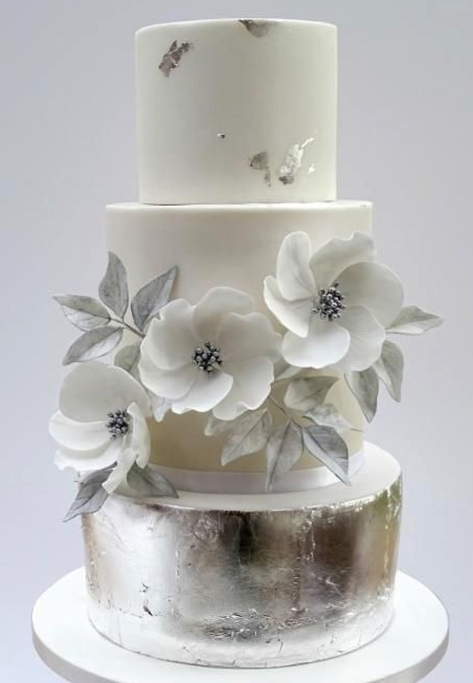 white and silver wedding cake with anemones flower