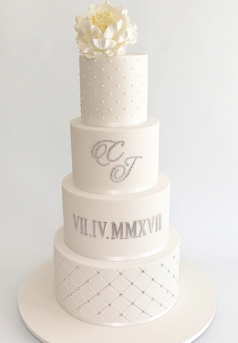 white and silver wedding cake with wedding date in roman numerals