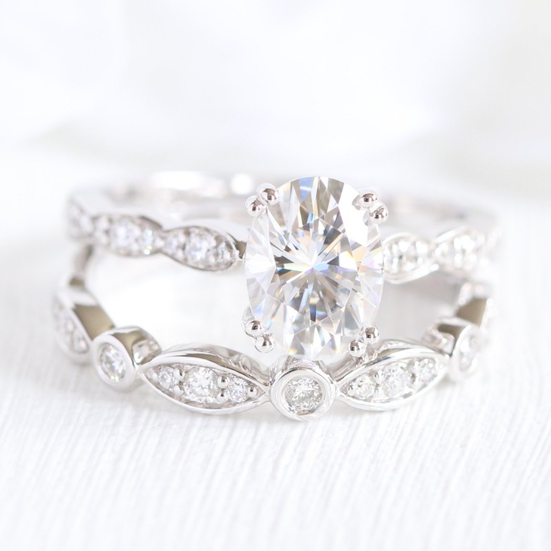 Exquisite bridal set of oval Moissanite engagement ring in solitaire design with scalloped diamond band paired with a bezel scalloped