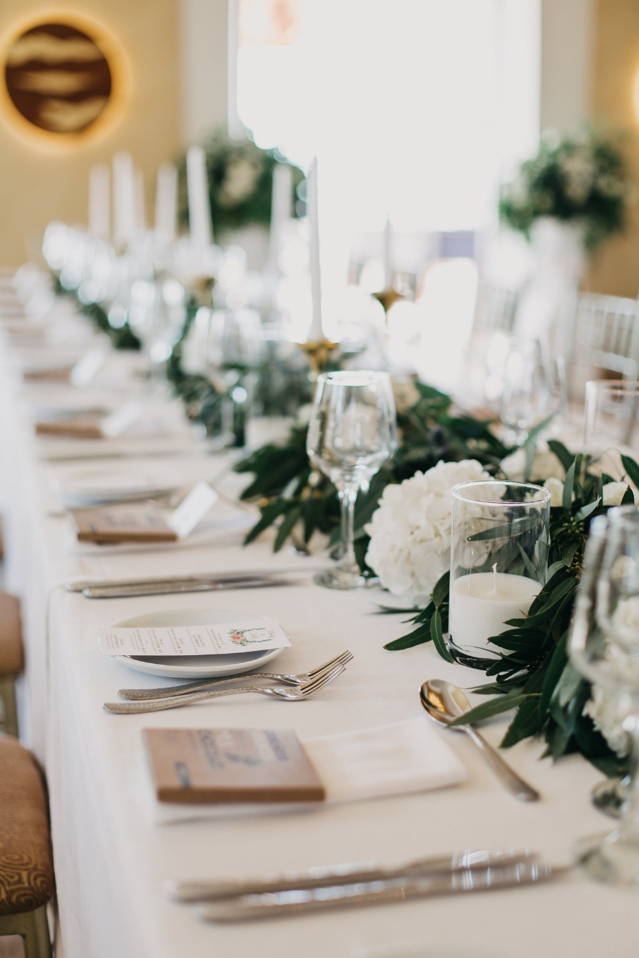 Reception table with greenery and white flowers