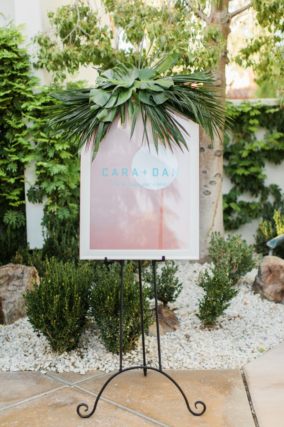 Custom designed wedding sign with tropical greenery