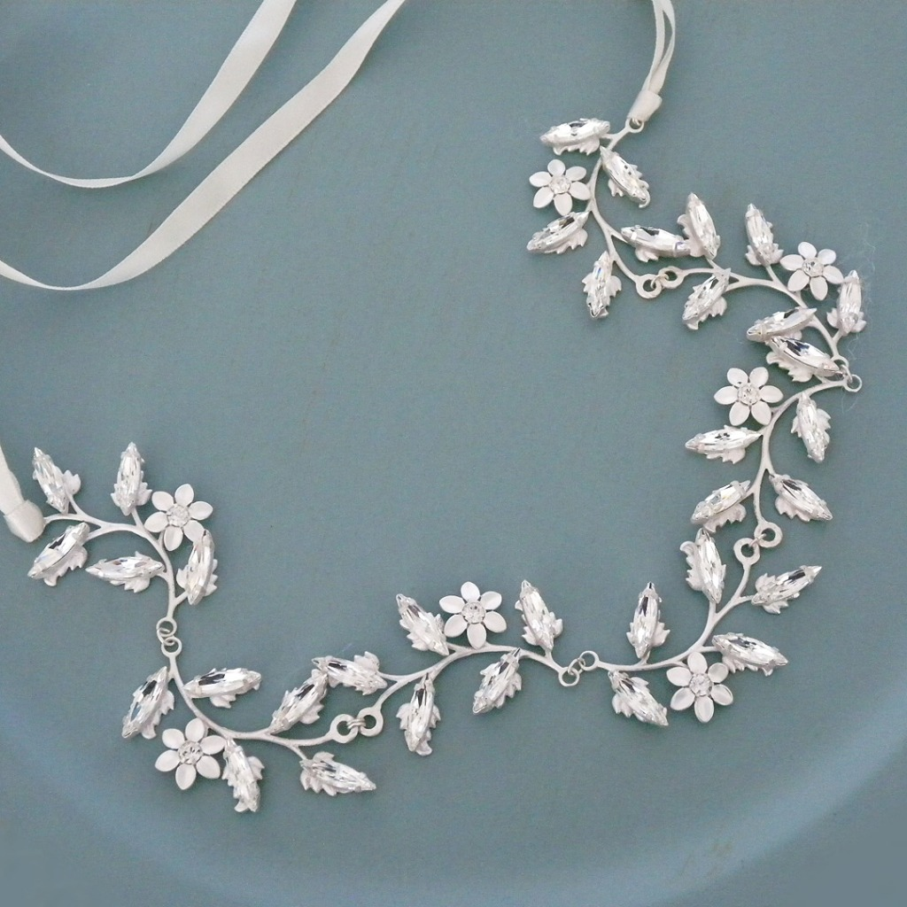 A flexible vine of matte silver leaves and flowers is adorned with crystals. So feminine. So pretty. Designed by Elizabeth Bowers.