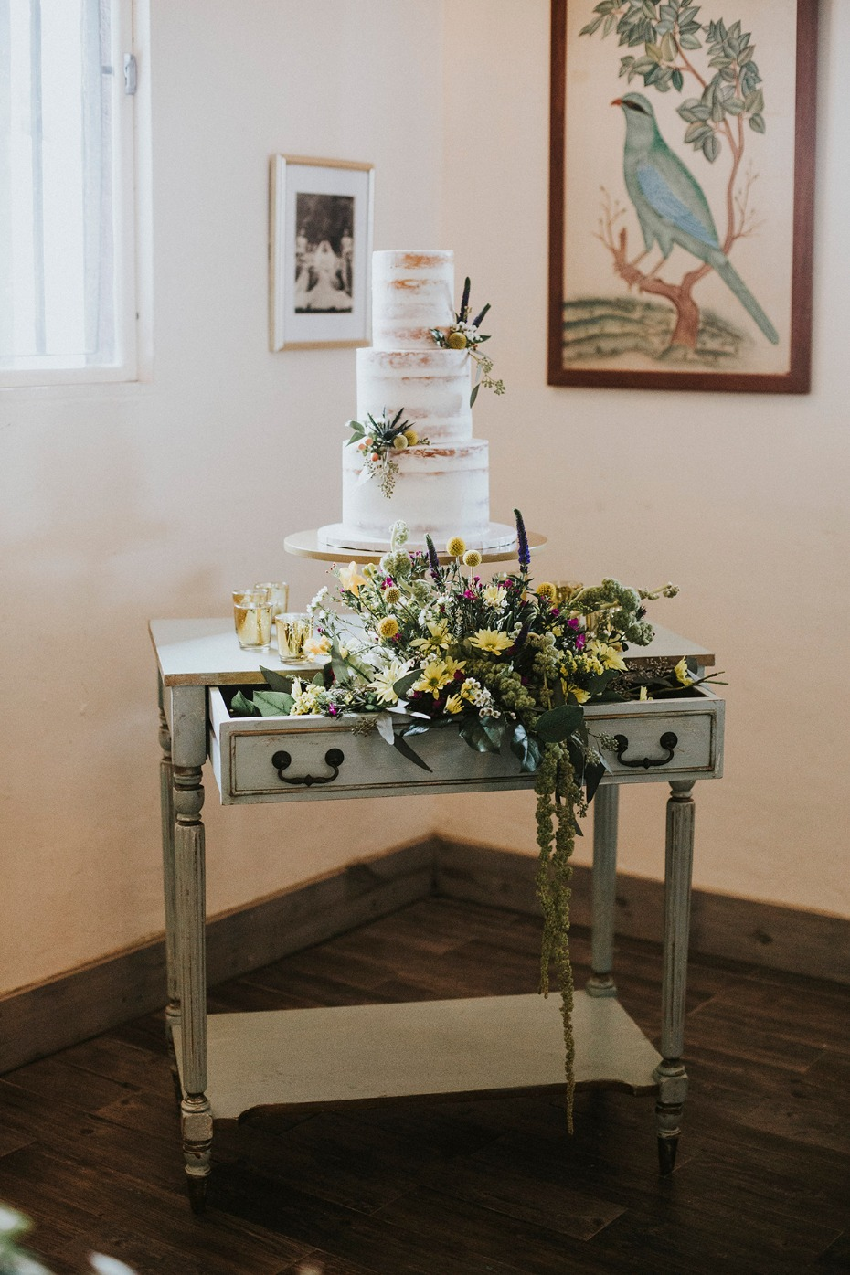 nearly naked wedding cake with vintage flower filled cake table