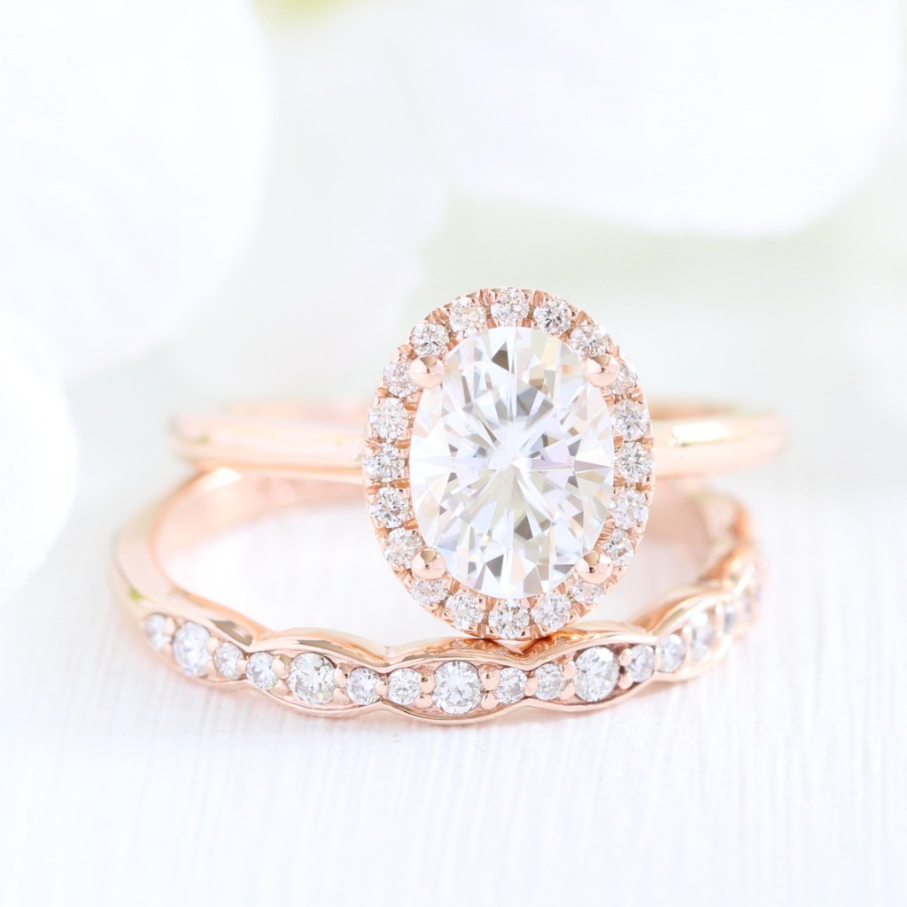 Classic Bridal Set of Oval Moissanite Diamond Halo Engagement Ring paired with a Scalloped Diamond Wedding Band in Rose Gold. See more
