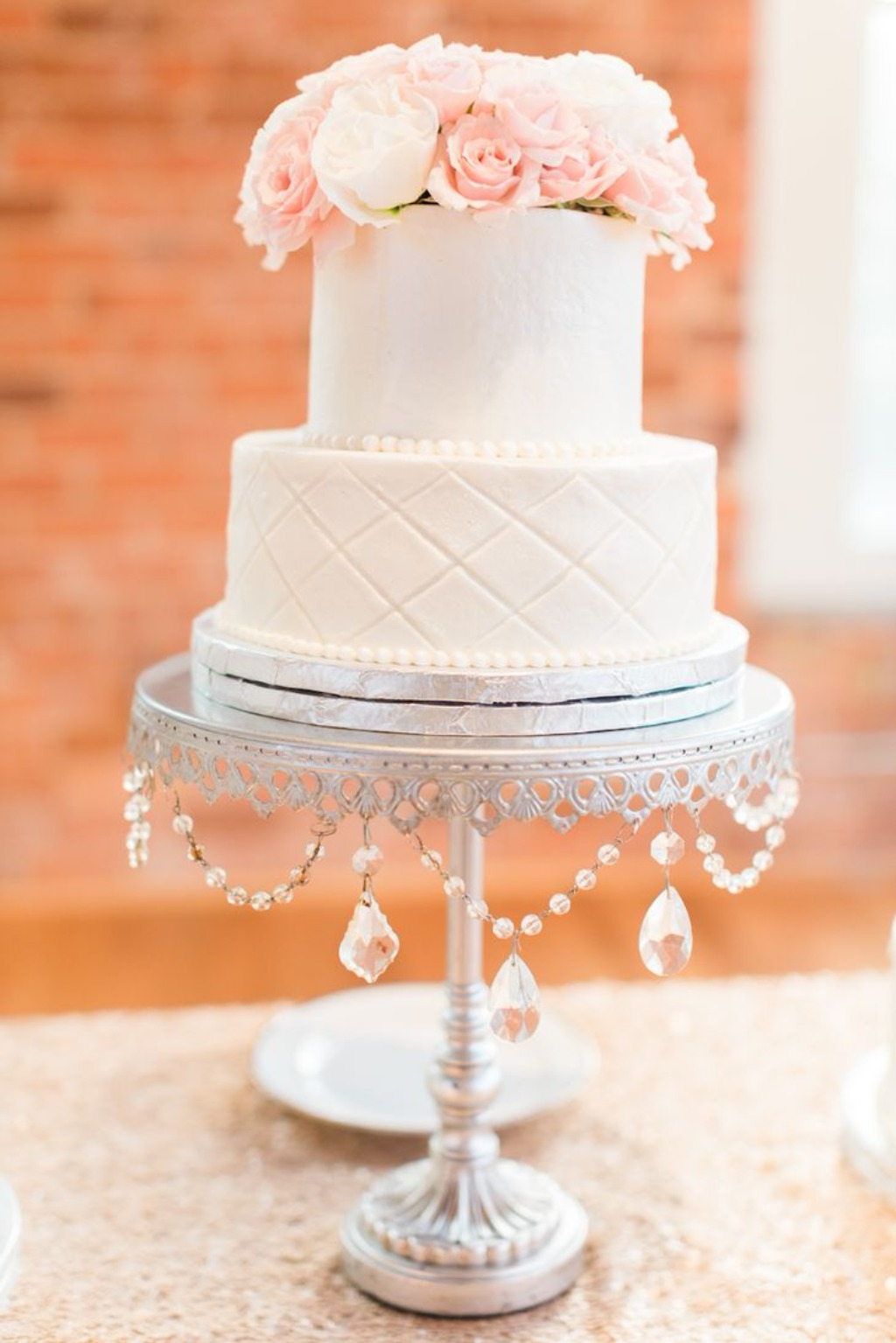 White tiered wedding cake, fresh flowers & silver chandelier accents!