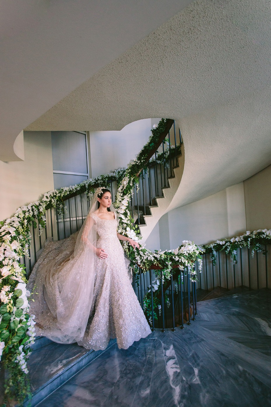 a bride descending a flower draped staircase
