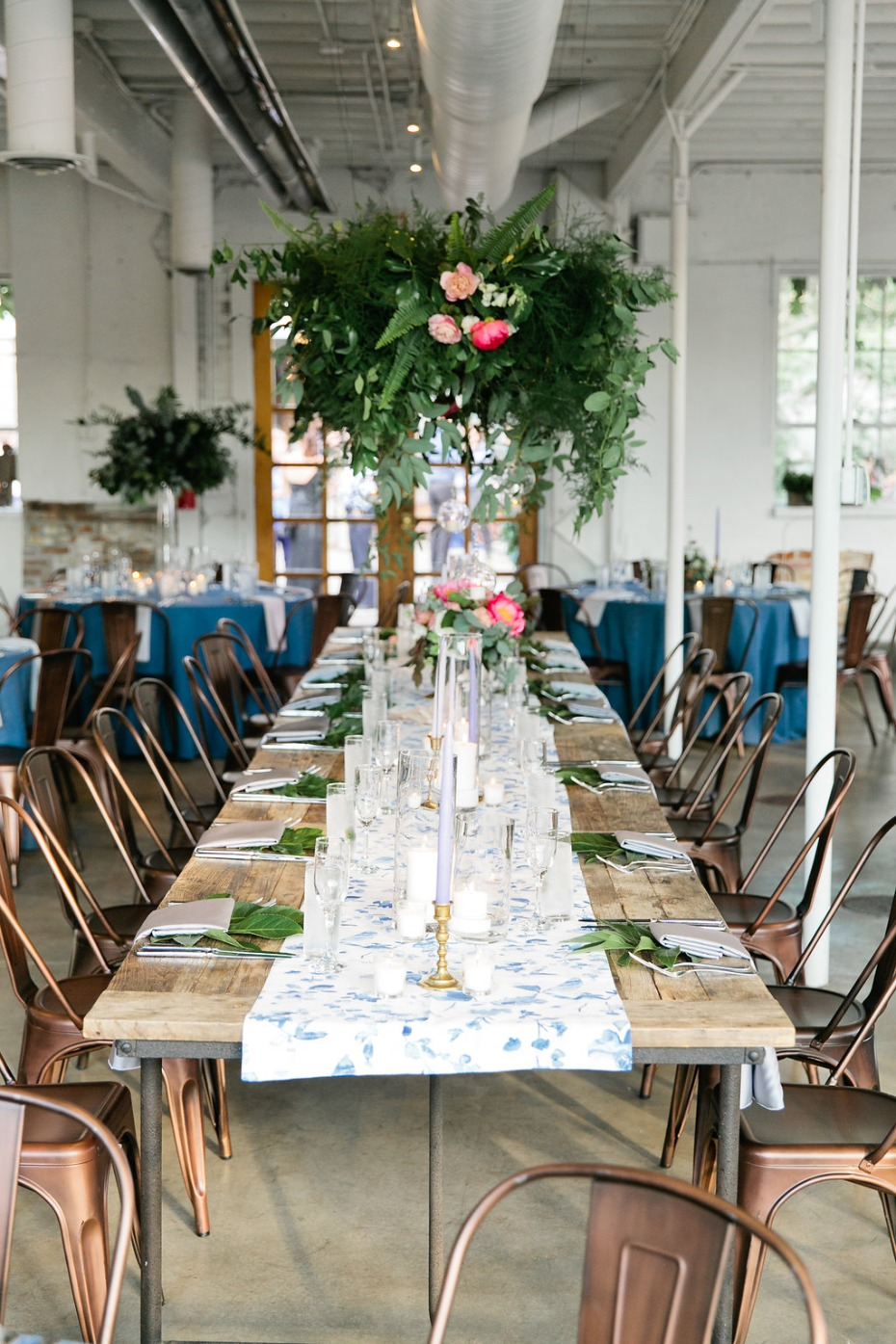 industrial chic head table idea with floral chandelier