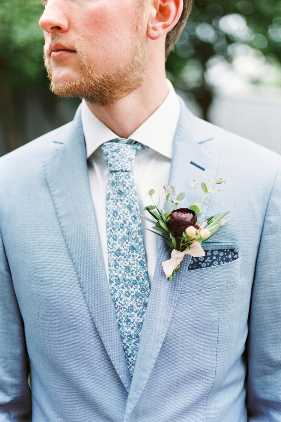 groom in light blue suit and floral tie and pocket square