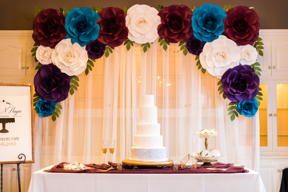 wedding cake table with paper flower backdrop