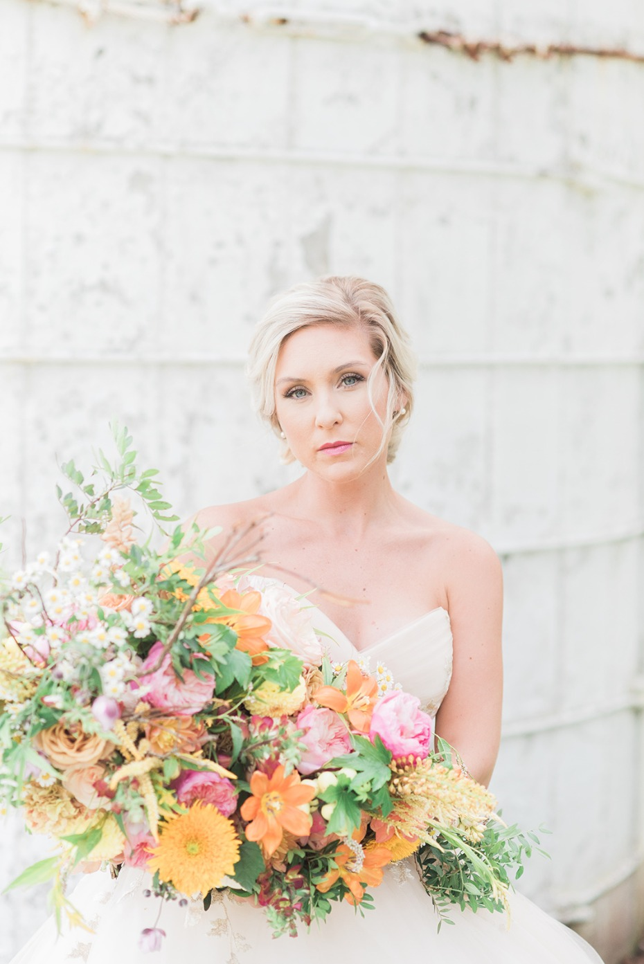 bride with bright orange and yellow bouquet