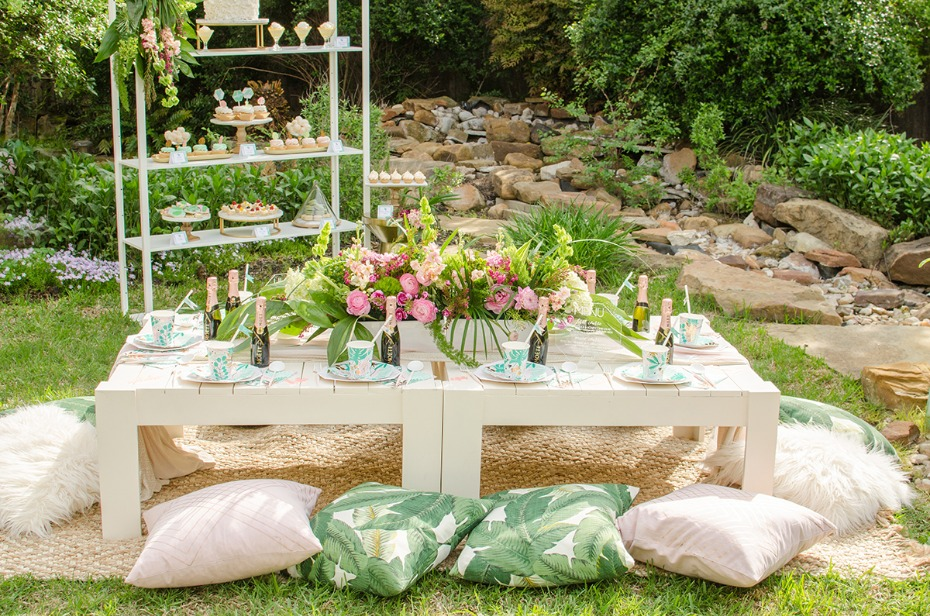 floor level party table with pink and green tropical decor