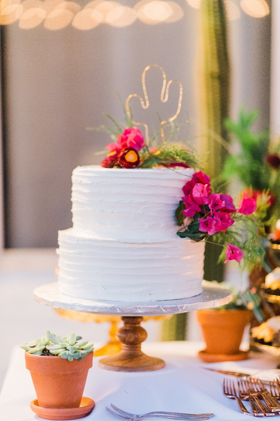 White wedding cake with a wire cactus topper