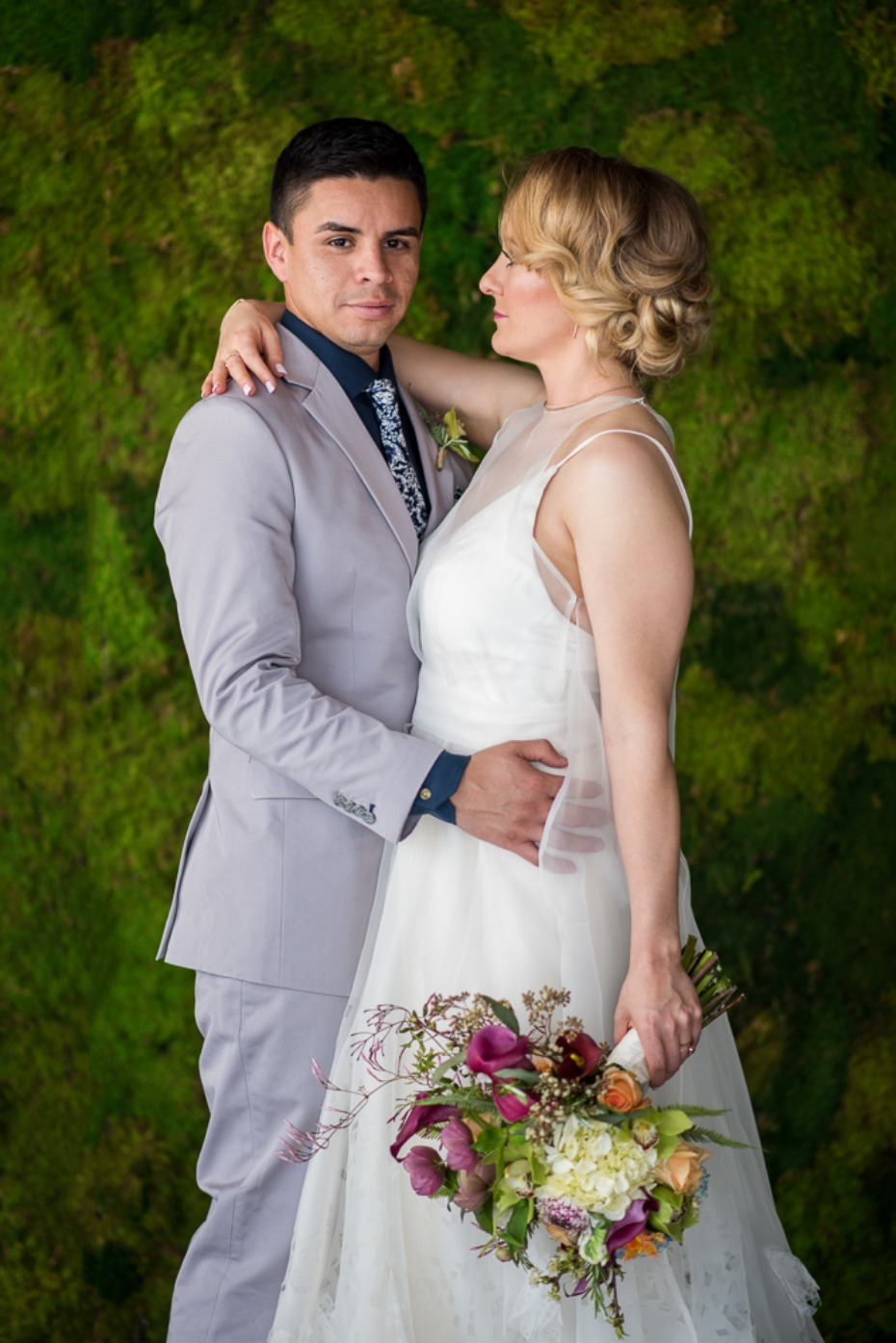 bride and groom and a moss wall