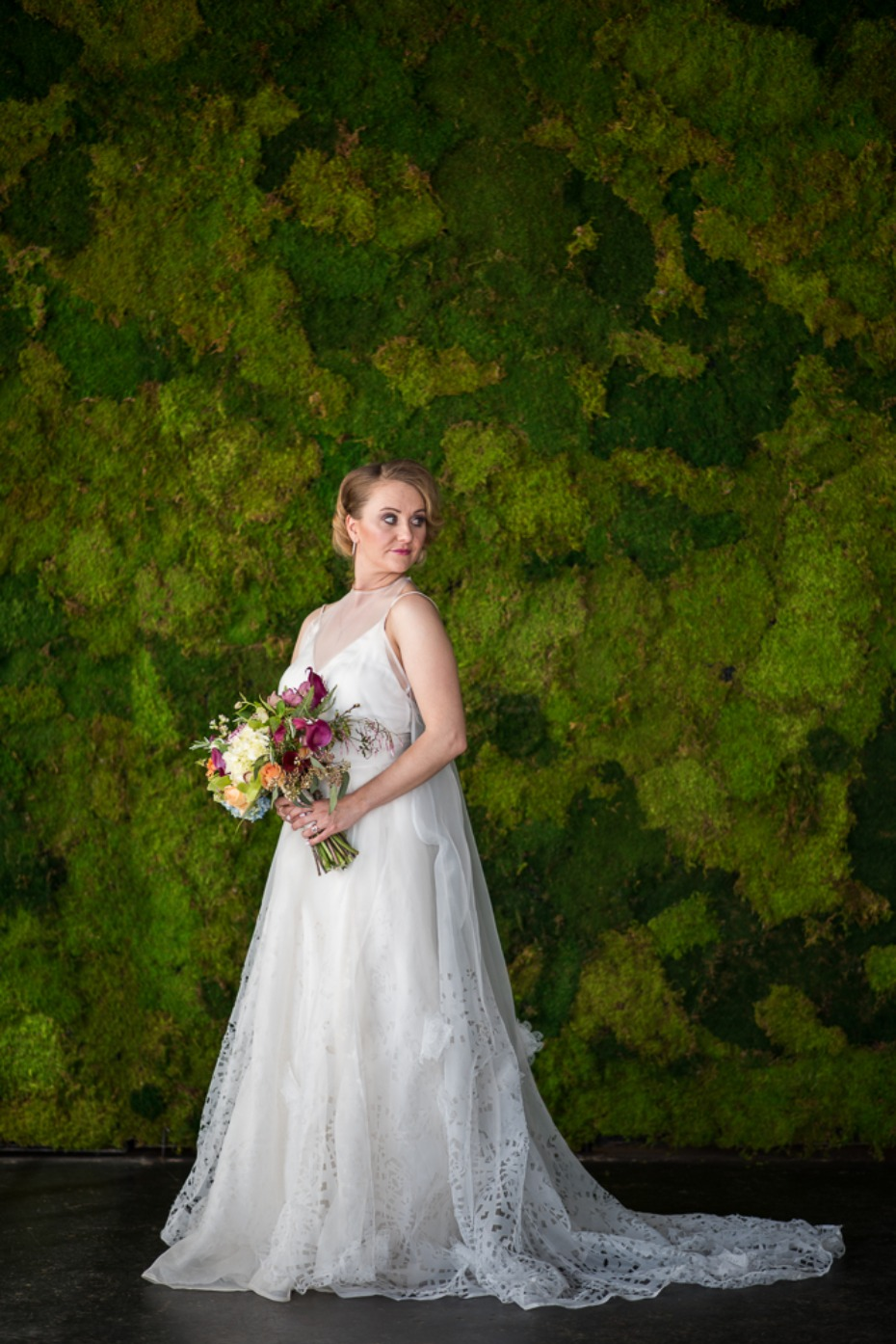 bride and a moss wall