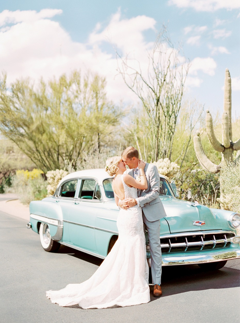 bride and groom and their wedding getaway car