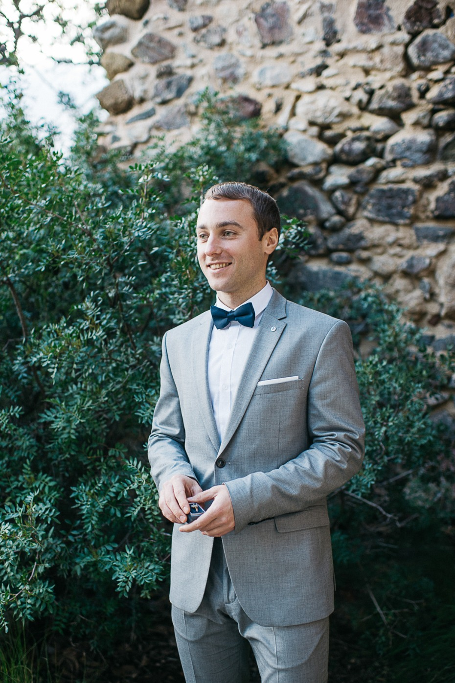 groom in light grey suite and bow tie