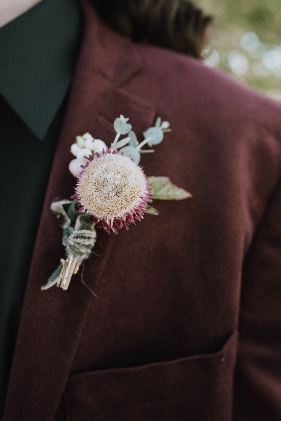 groom in burgundy and black