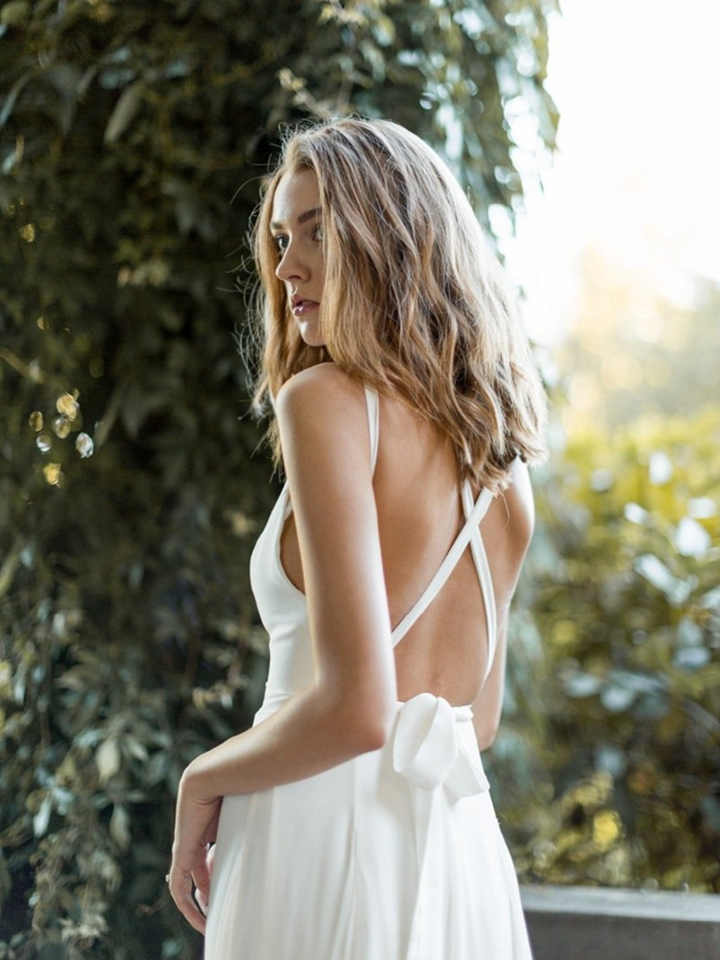Ines boasts an open back with criss-cross straps that hold the bodice snug while letting the train flow free. Perfect for bohemian