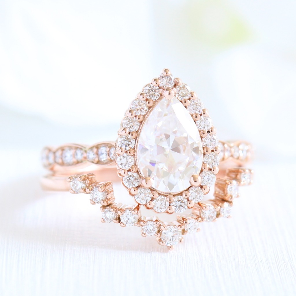 Feast your eyes on this unique-in-every-way bridal set of a Pear Moissanite Halo Diamond Engagement Ring in Scalloped Band paired with