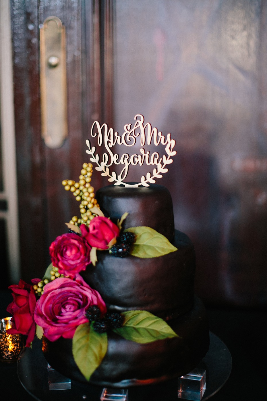 Black wedding cake with pink and red florals