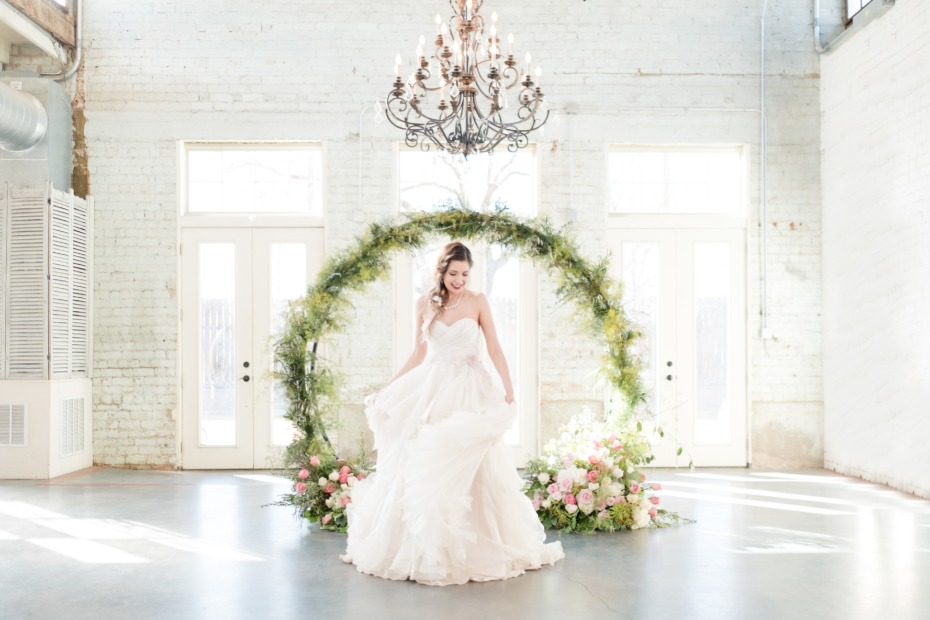 bride in front of a floral arch