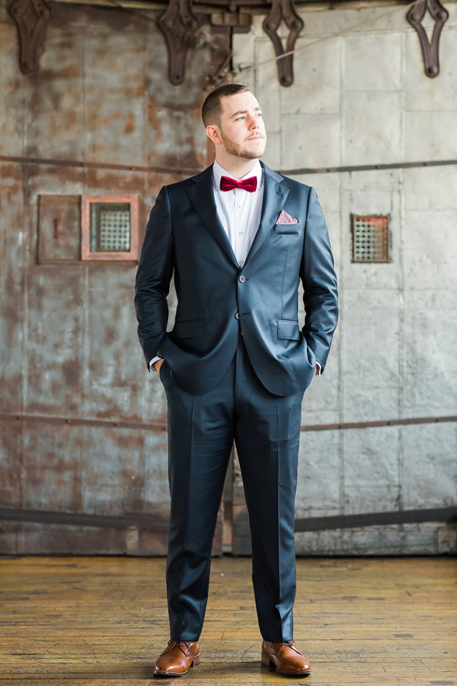 groom in navy suite and red bow tie