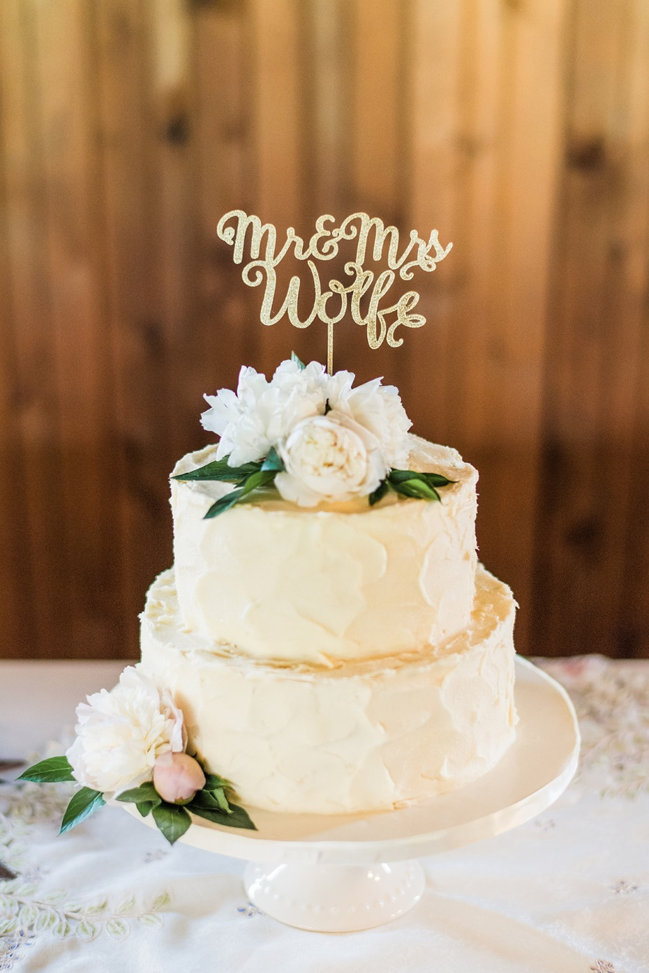 dirty frosted wedding cake with floral topper