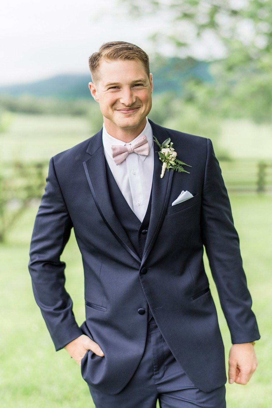 groom in soft pink bow tie and navy suit