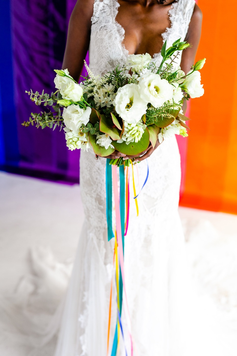all white wedding bouquet with rainbow bouquet ribbons