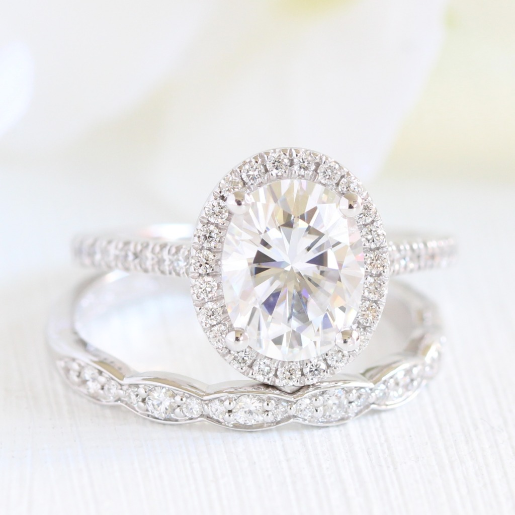 Halo of diamonds surrounding a gorgeous Oval Moissanite? and a scalloped diamond wedding band to complete the look? Who could say no