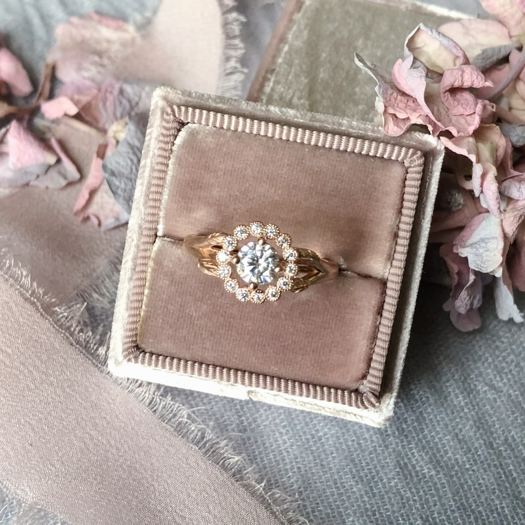 Our new vintage inspired Gwendolyn Ring in 14k Rose Gold. It has delicate migrain detailing around the halo and leaves trailing up