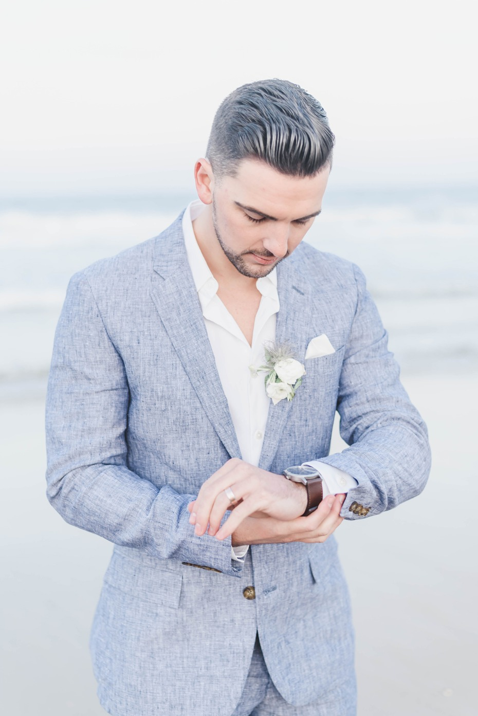 groom in heather grey suit for the beach