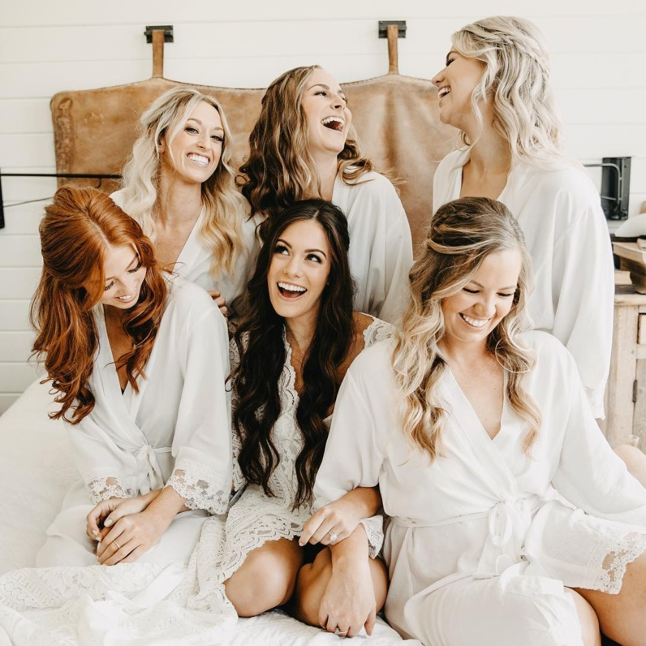 Happy bridesmaids lounging in bed