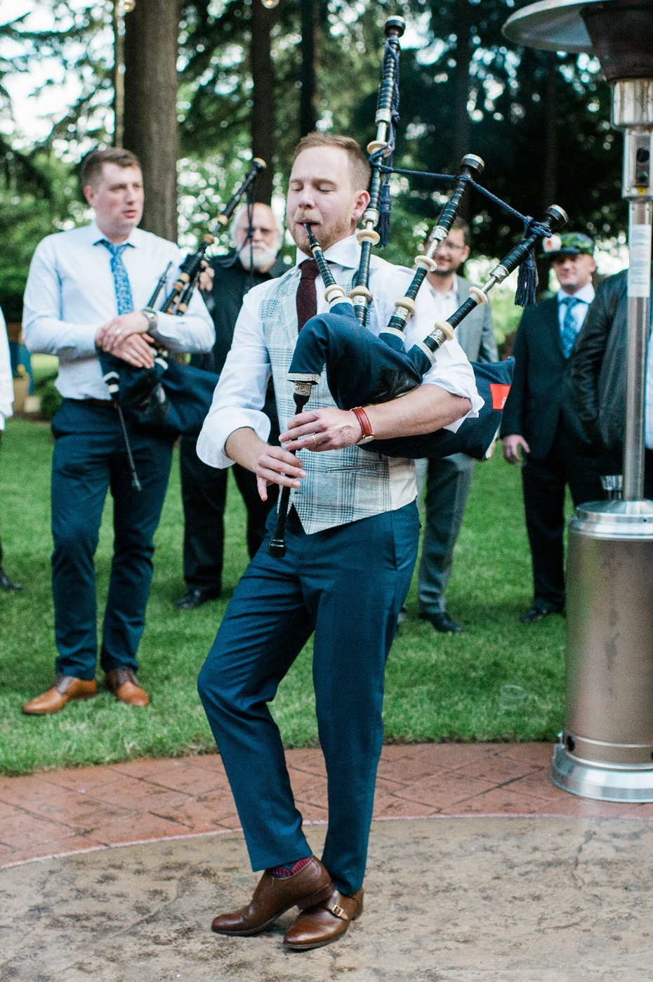 groom playing the bagpipes for his new wife