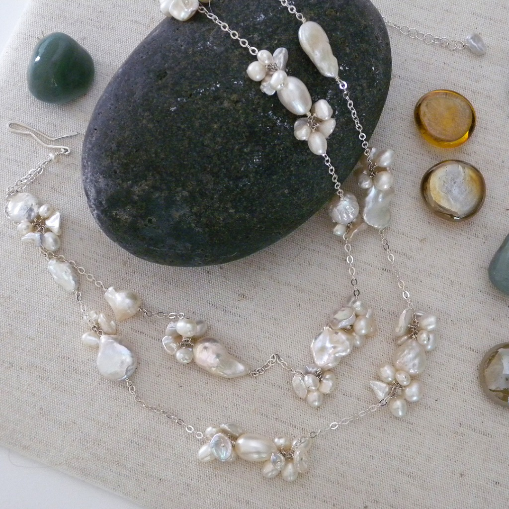Various clusters of natural freshwater pearls in baroque, coin, Keishi and round styles are uniquely assembled on a sterling silver
