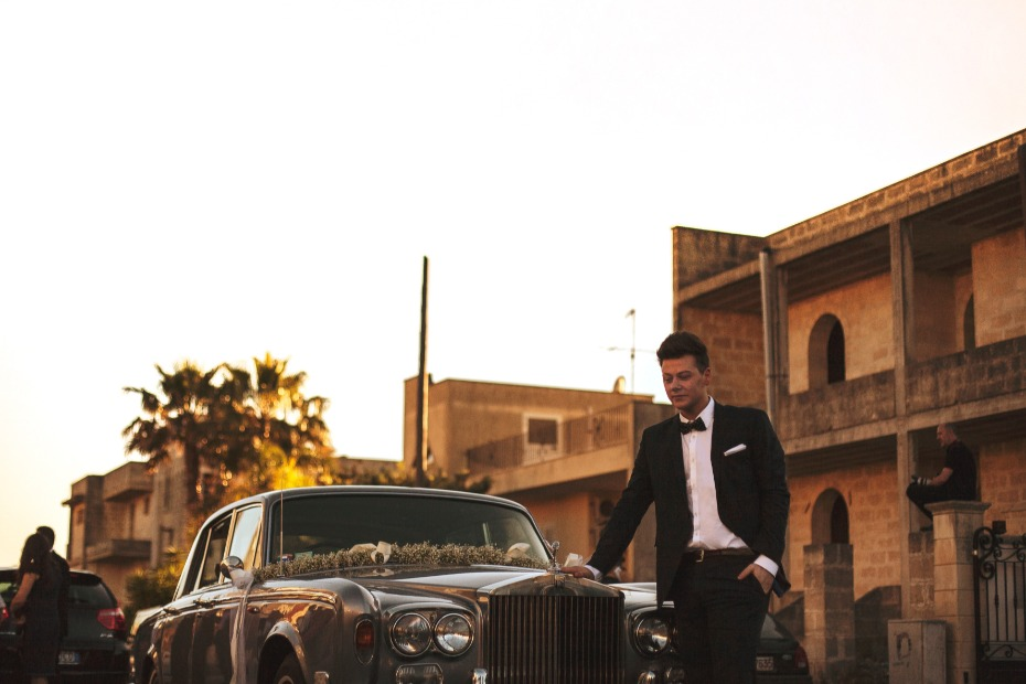 Groom standing in front of rolls royce
