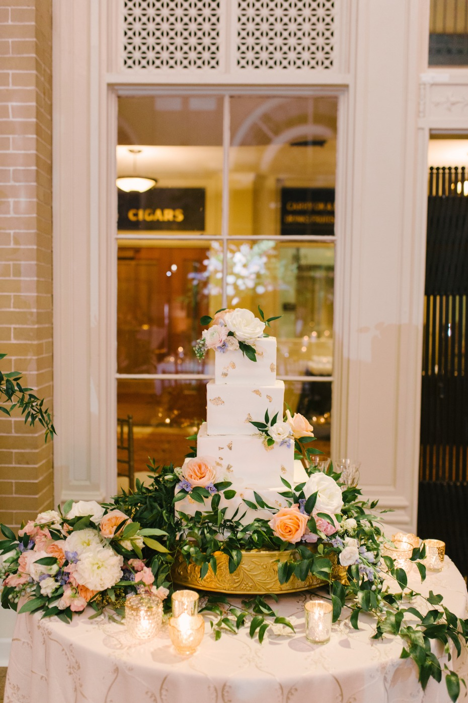 wedding cake table with cascading floral decor