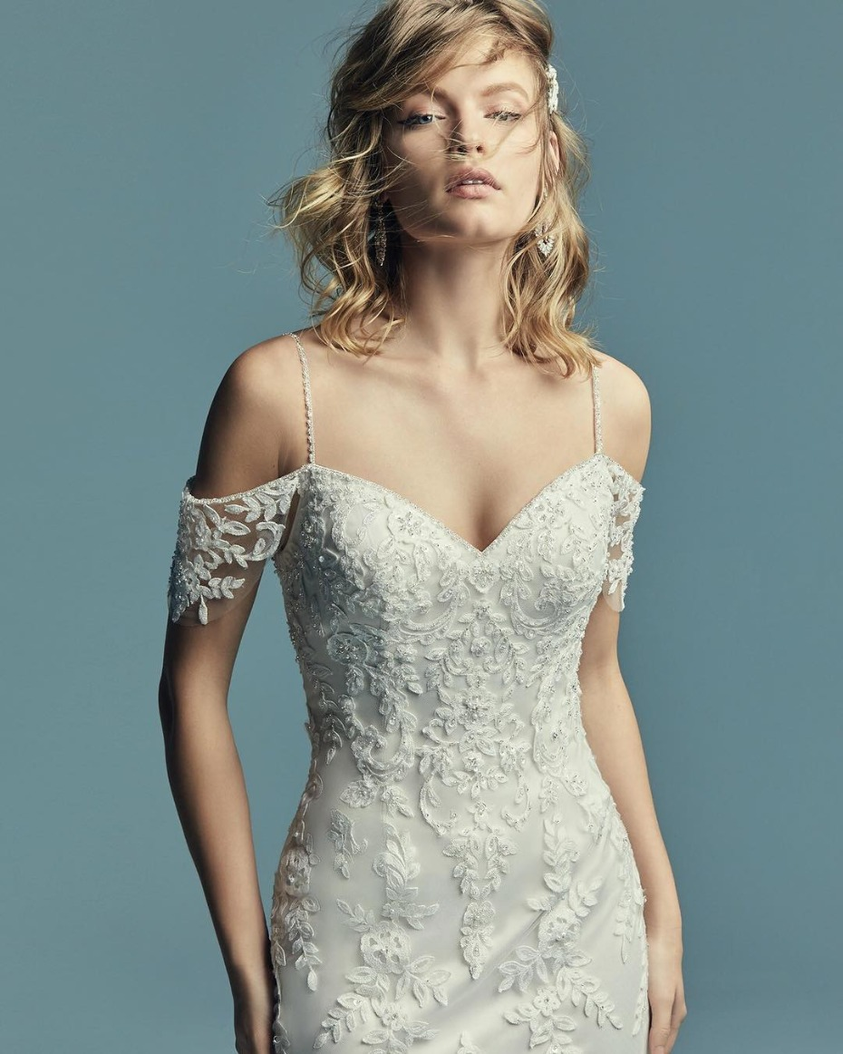 Maggie Sottero Angelica Gown: Sheath wedding dress with cascading lace motifs over tulle, illusion cold-shoulder sleeves and beaded spaghetti straps