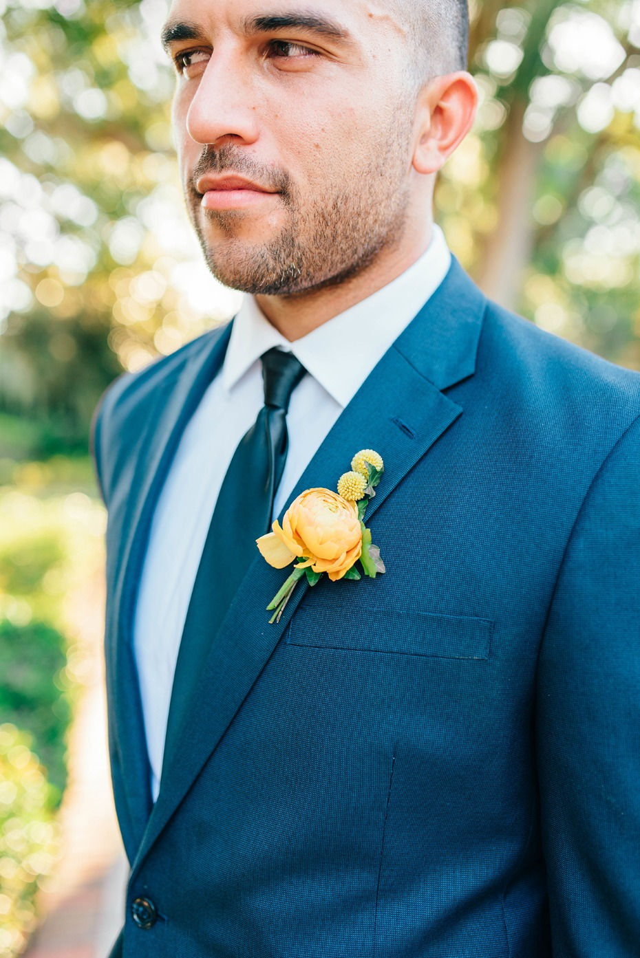groom in blue suite and golden floral boutonniere