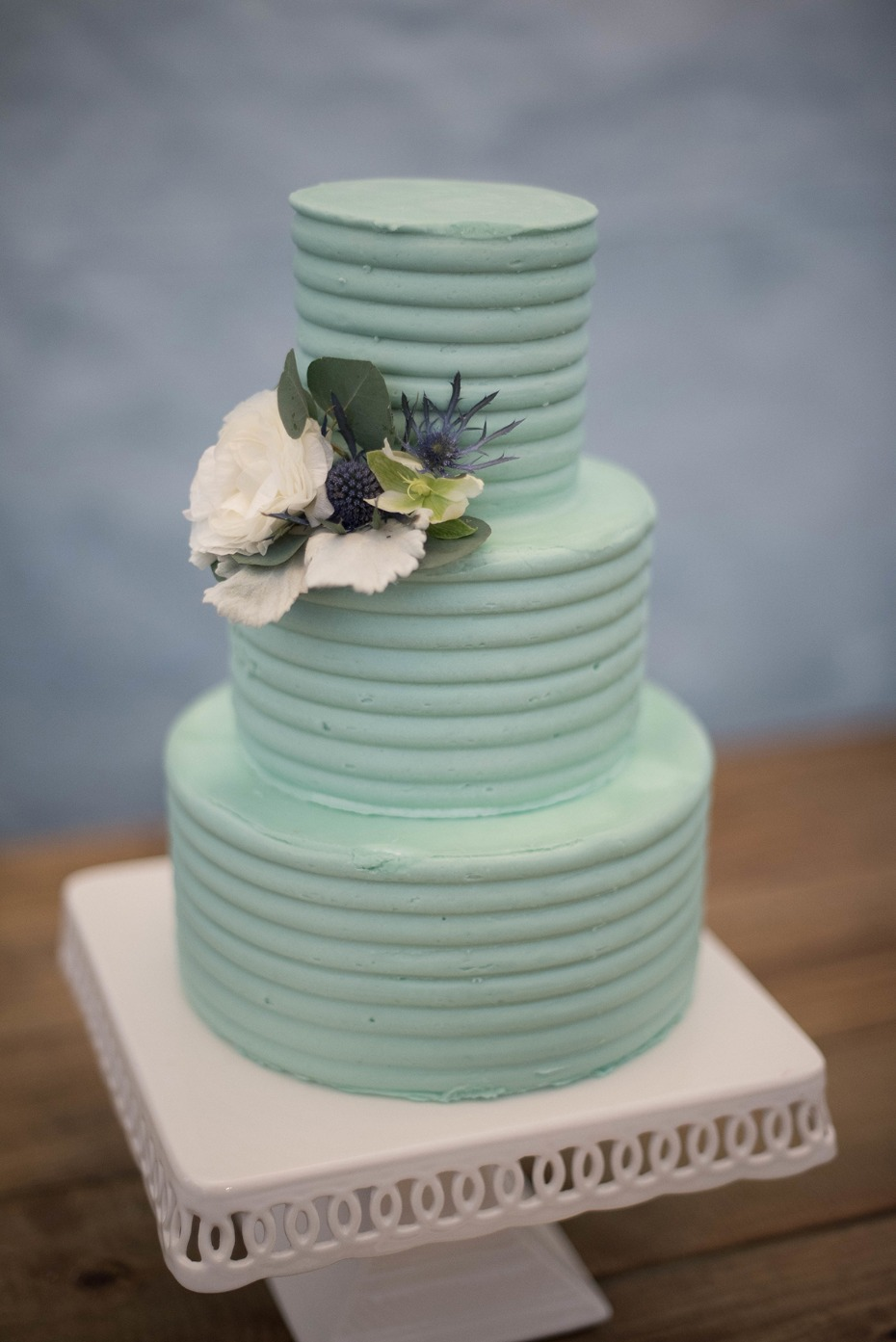 teal wedding cake topped with florals