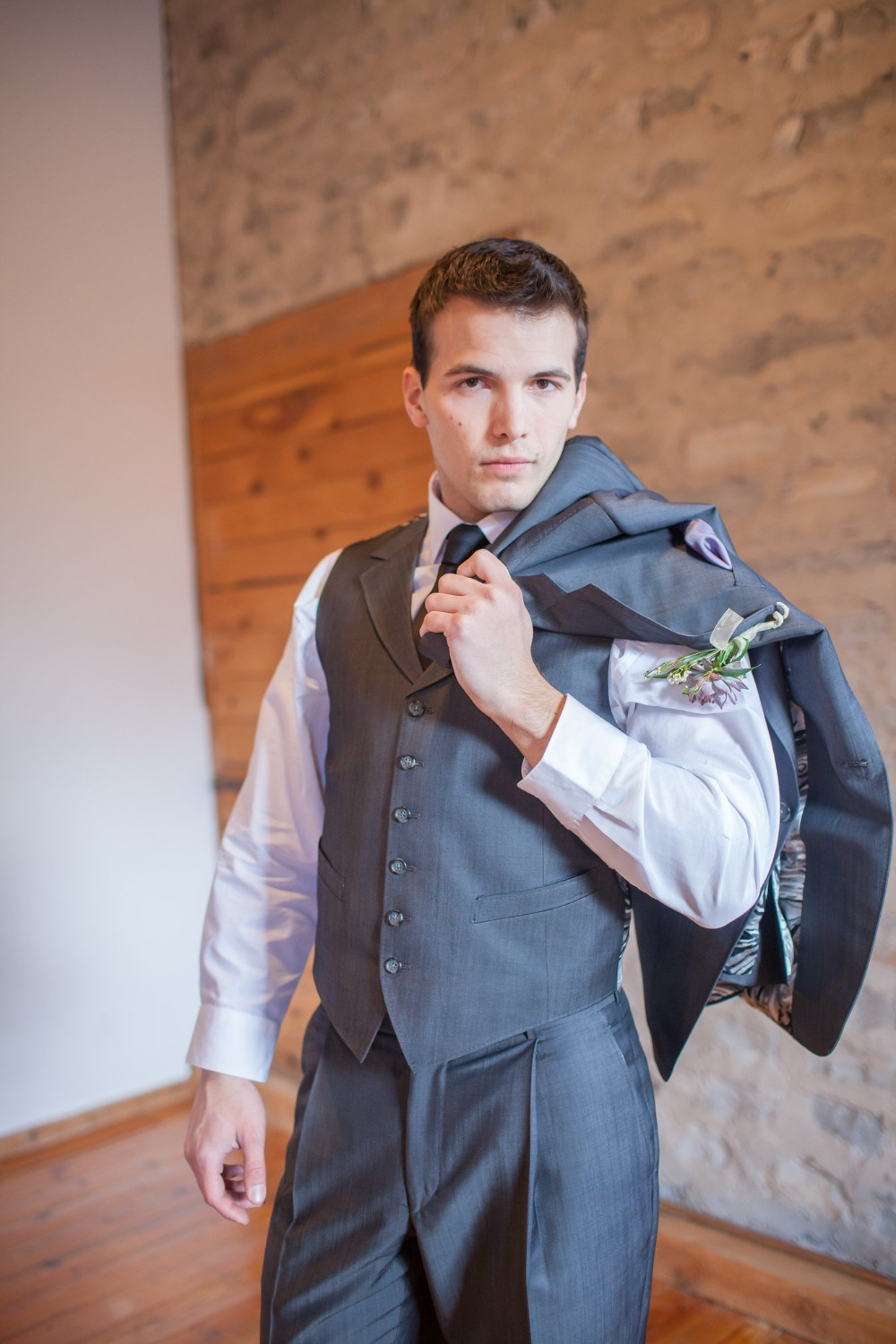 groom in three piece grey suit