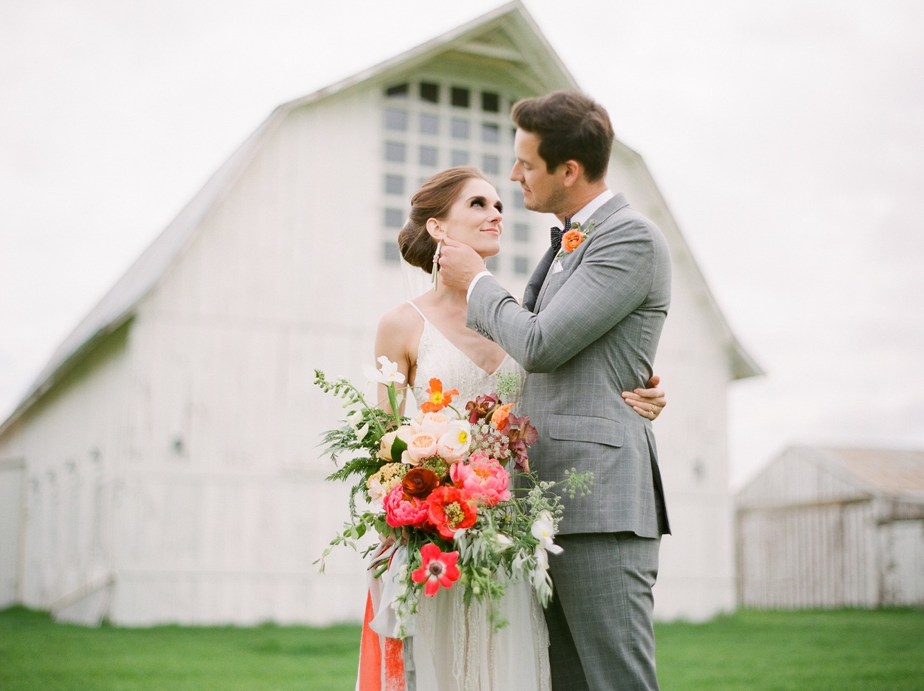 wedding couple at white barn wedding venue in Idaho