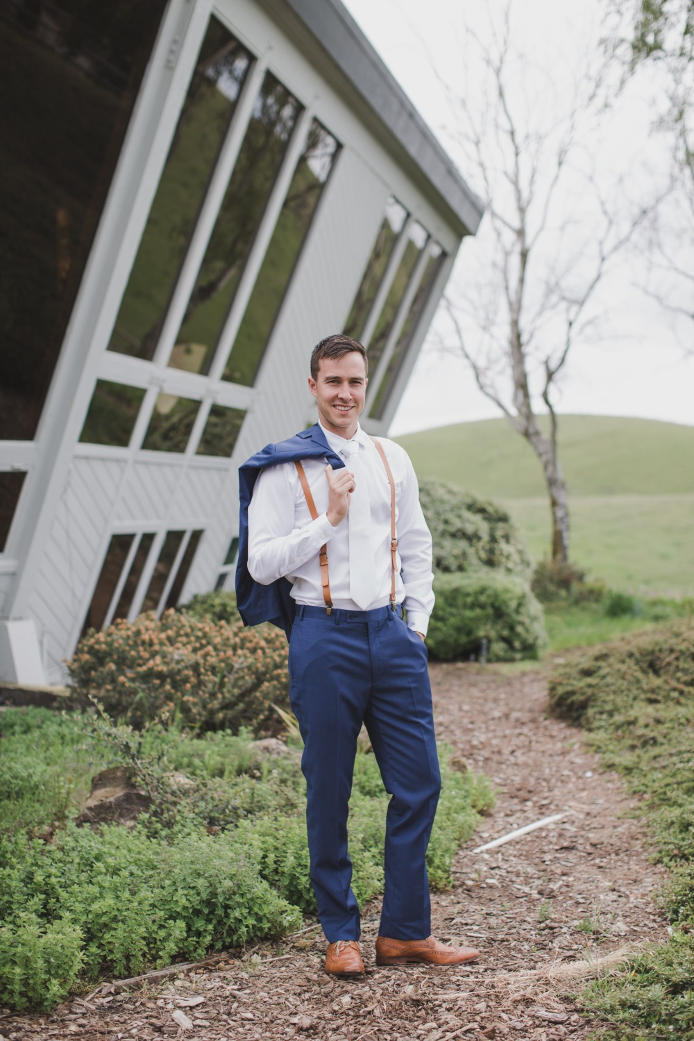 white and navy Groom outfit idea with leather suspenders