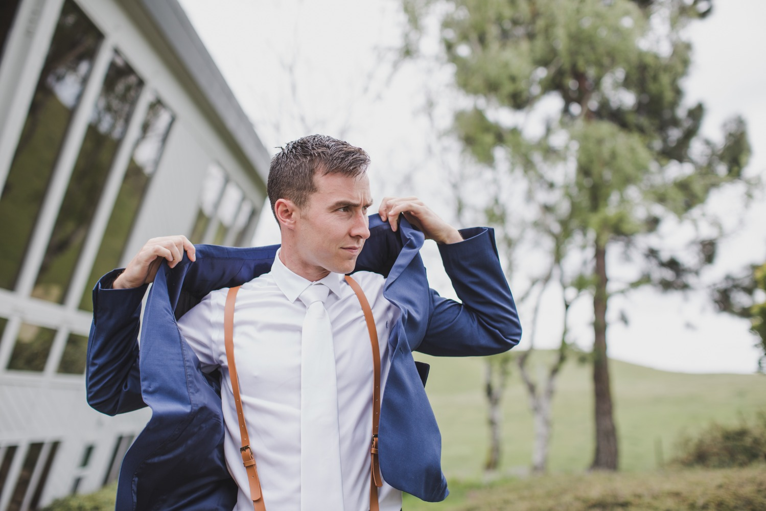 blue and white groom with leather suspenders