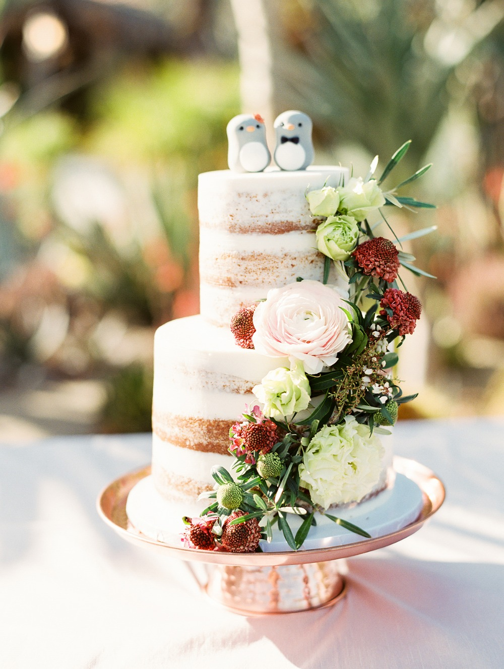 nearly naked wedding cake with penguin toppers