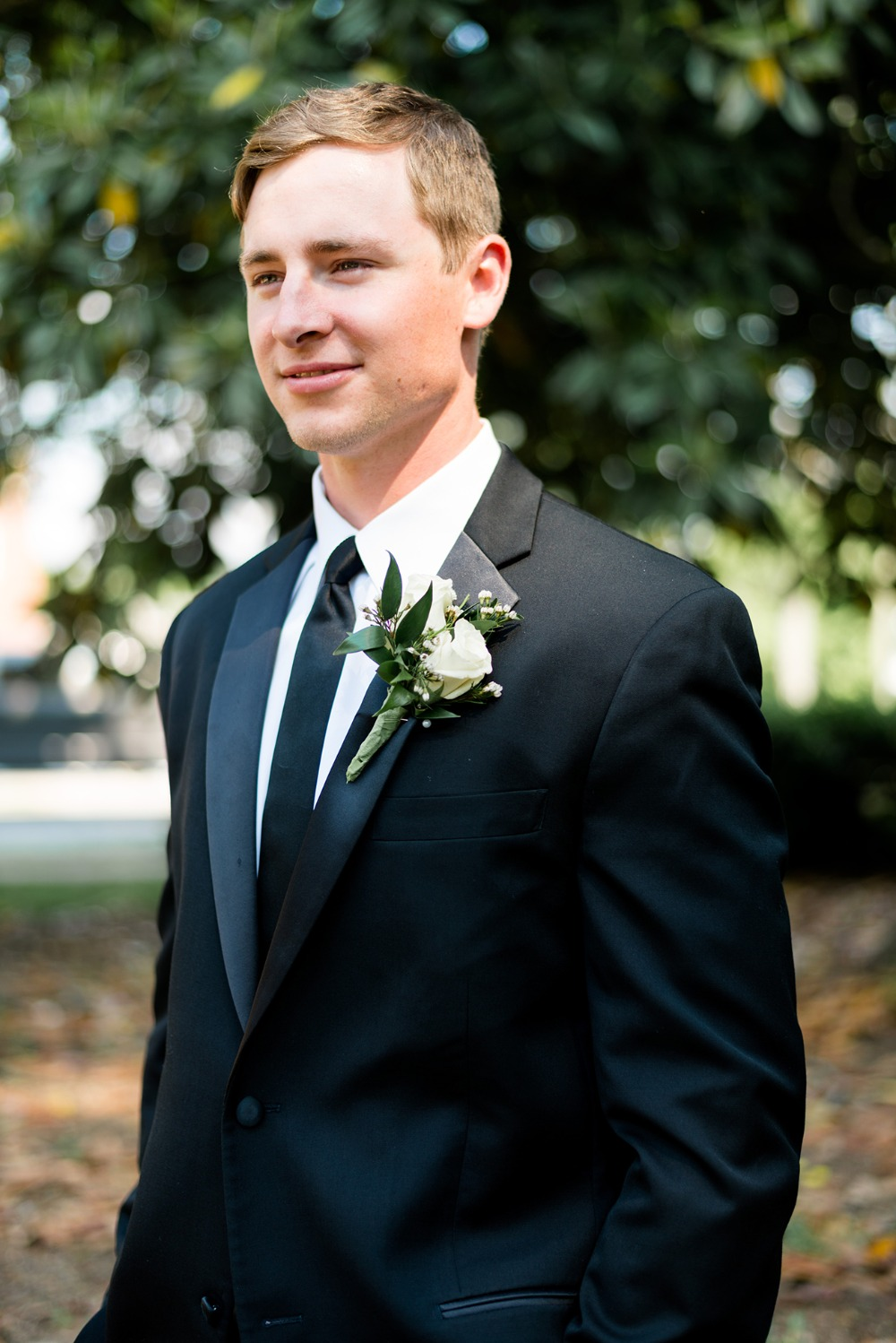 groom in classic black suit